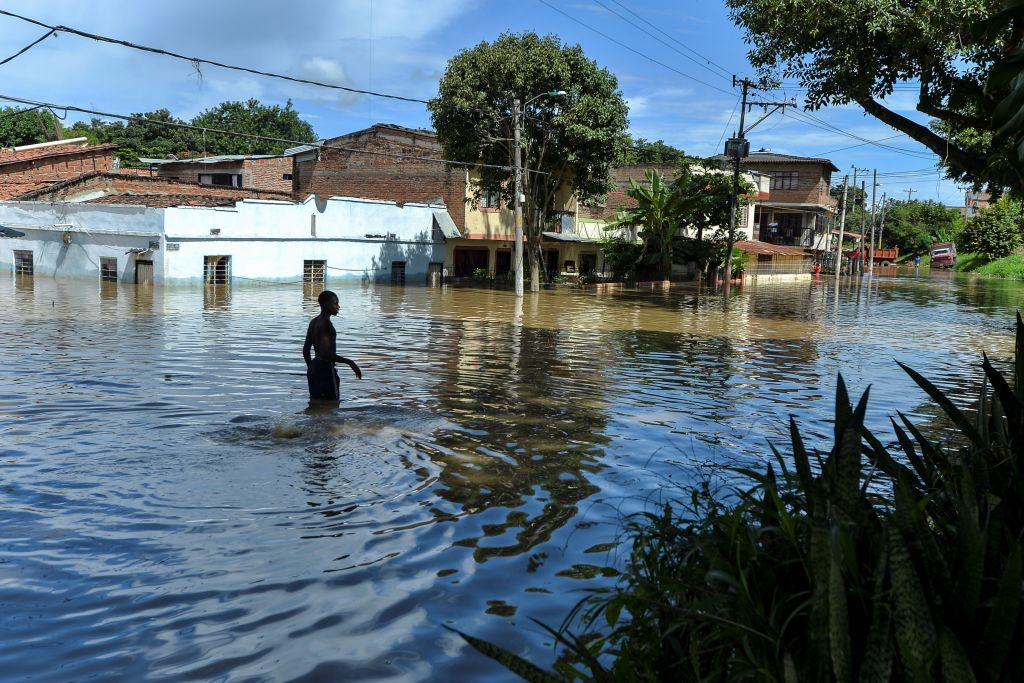 A man wades through the water in a flooded area of Cali, Colombia, on May 13, 2017 after heavy rains caused the overflowing of the Cauca river. Flooding and mudslides in Colombia have killed several people and affected thousands in the past weeks causing alarm in a country still recovering from recent mudslides that killed hundreds. / AFP PHOTO / LUIS ROBAYO (Photo credit should read LUIS ROBAYO/AFP/Getty Images)