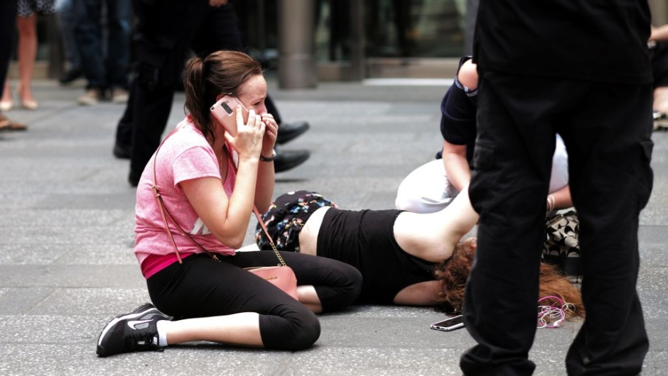 EDITORS NOTE: Graphic content / A woman makes a phone call as others attend to an injured person after a car plunged into them in Times Square in New York on May 18, 2017. A car plowed into a crowd of pedestrians in New York's bustling Times Square, leaving one person dead and at least 19 others injured in what officials said was an accident. / AFP PHOTO / Jewel SAMAD (Photo credit should read JEWEL SAMAD/AFP/Getty Images)