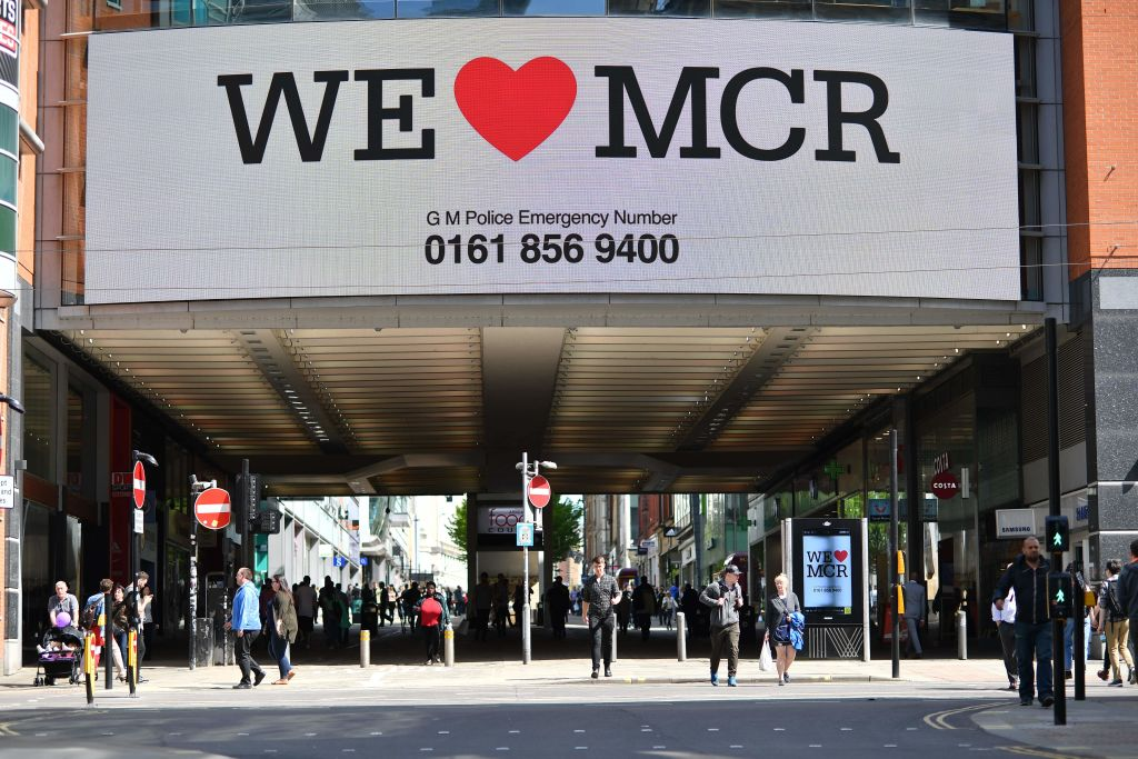"""A sign that reads """"We Love MCR"""" is displayed in solidarity above a street in central Manchester, northwest England on May 23, 2017 following a deadly terror attack at a concert at the Manchester Arena the night before. Twenty two people have been killed and dozens injured in Britain's deadliest terror attack in over a decade after a suspected suicide bomber targeted fans leaving a concert of US singer Ariana Grande in Manchester. / AFP PHOTO / Ben STANSALL (Photo credit should read BEN STANSALL/AFP/Getty Images)"""