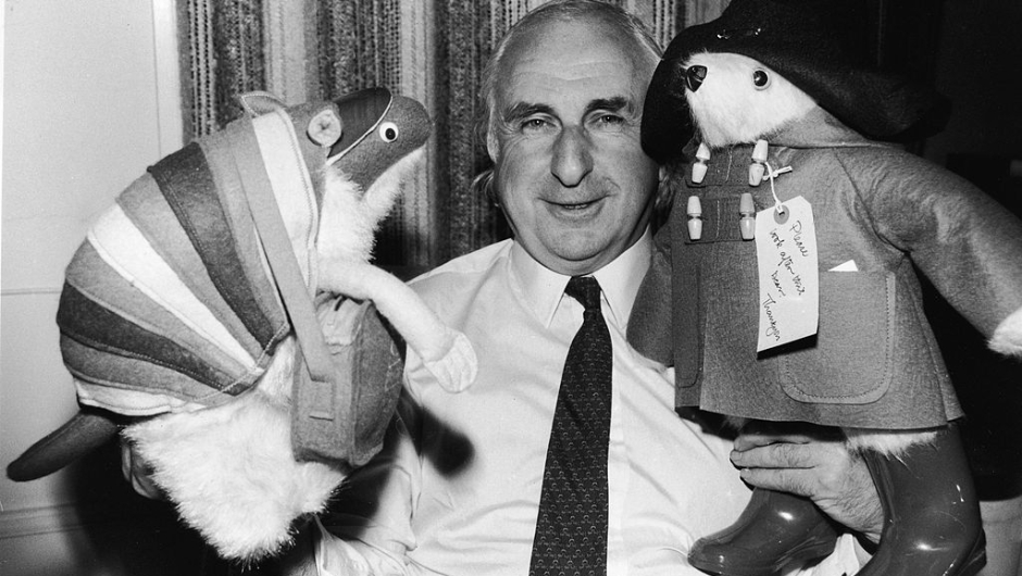 British children's book author Michael Bond stands with stuffed animal toys of his characters Paddington Bear and J.D. Polson the Armadillo, June 27, 1981. (Photo by Larry Ellis/Express Newspapers/Getty Images)