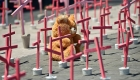 A wooly bear from a victim of femicide are pictured next to crosses during a protest against the murder of more than 600 women in the last four years, in Ecatepec, State of Mexico, on March 13 , 2016. AFP PHOTO/RONALDO SCHEMIDT / AFP / RONALDO SCHEMIDT (Photo credit should read RONALDO SCHEMIDT/AFP/Getty Images)
