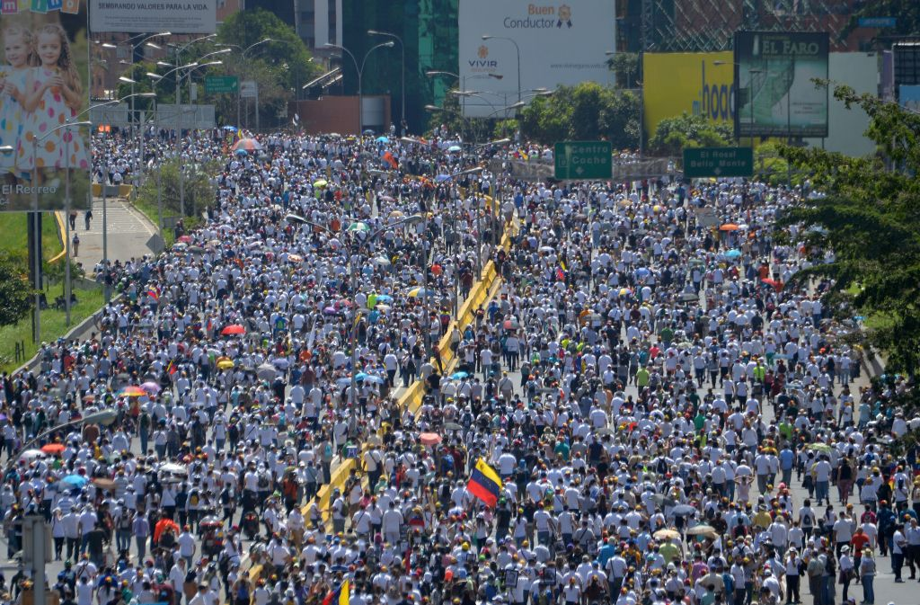 TOPSHOT - Opposition activists march against President Nicolas Maduro's government in Caracas, on May 29, 2017. Demonstrations that got underway in late March have claimed the lives of 59 people, as opposition leaders seek to ramp up pressure on Venezuela's leftist president, whose already-low popularity has cratered amid ongoing shortages of food and medicines, among other economic woes. / AFP PHOTO / LUIS ROBAYO (Photo credit should read LUIS ROBAYO/AFP/Getty Images)