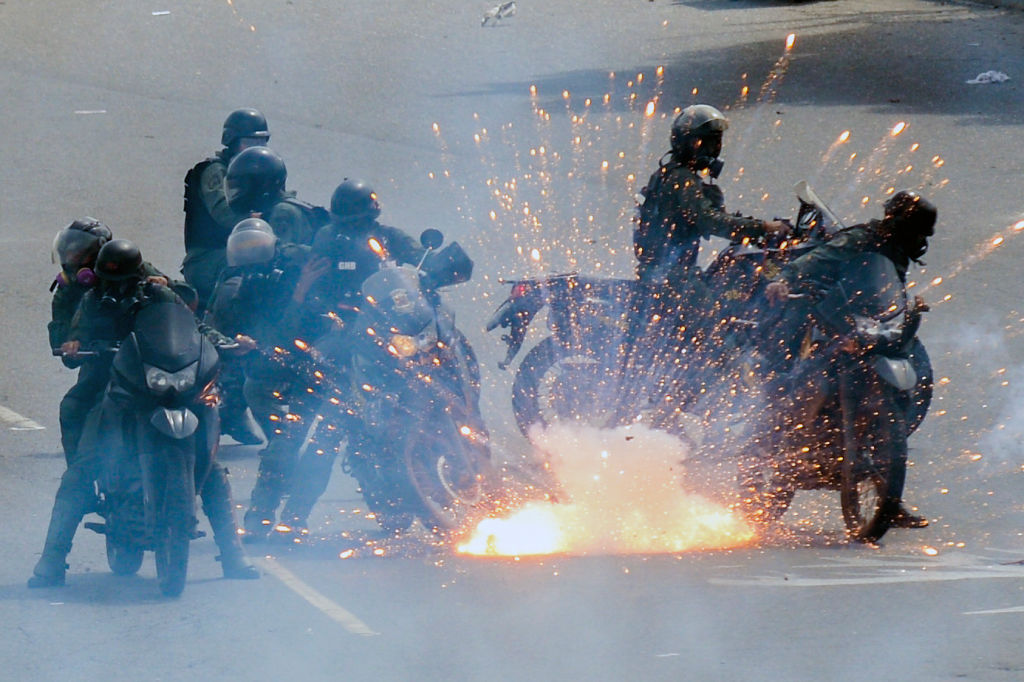 """TOPSHOT - A firework launched by opposition activists explodes amid a group of National Guard riot police motorcyclists during a protest against President Nicolas Maduro's government, in Caracas on May 31, 2017. Venezuelan authorities on Wednesday began signing up candidates for a planned constitutional reform body, a move that has inflamed deadly unrest stemming from anti-government protests. Opponents of socialist President Nicolas Maduro say he aims to keep himself in power by stacking the planned """"constituent assembly"""" with his allies. / AFP PHOTO / FEDERICO PARRA (Photo credit should read FEDERICO PARRA/AFP/Getty Images)"""