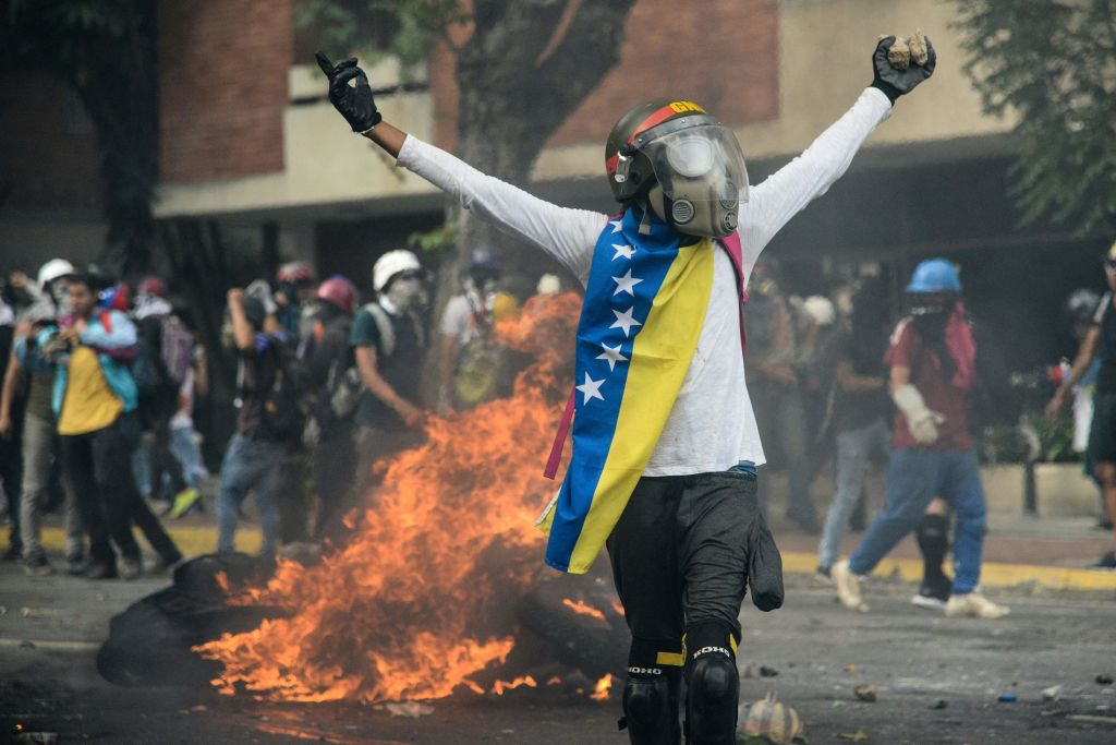TOPSHOT - Opposition demonstrators clash with riot police in Caracas, on May 31, 2017. Venezuelan authorities on Wednesday began signing up candidates for a planned constitutional reform body, a move that has inflamed deadly unrest stemming from anti-government protests. / AFP PHOTO / FEDERICO PARRA (Photo credit should read FEDERICO PARRA/AFP/Getty Images)