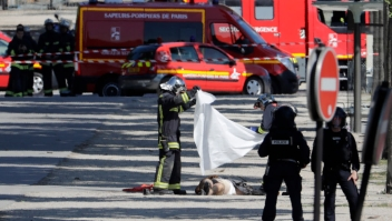 """TOPSHOT - EDITORS NOTE: Graphic content / Rescuers cover with a white sheet the body of a man lying in a sealed off area of the Champs-Elysees avenue in Paris, on June 19, 2017 , after a car crashed into a police van before bursting into flames, with the driver being armed, probe sources said. A car burst into flames after it crashed into a police van on the Champs-Elysees avenue in Paris on June 19, police and investigators said, adding that the driver was armed and it appeared to be a """"deliberate"""" act. Authorities said the driver was """"most probably dead"""". / AFP PHOTO / Thomas SAMSON (Photo credit should read THOMAS SAMSON/AFP/Getty Images)"""