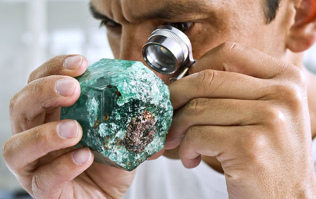 "A worker looks at an emerald at the workshop of Muzo Emerald Company in Bogota, on October 16, 2015. Colombian emeralds are considered to be the most beautiful in the world, but the same as ""blood diamonds"" of Africa, their image was saddened by decades of violence, a reputation some are willing to change. AFP PHOTO/Luis Acosta (Photo credit should read LUIS ACOSTA/AFP/Getty Images)"