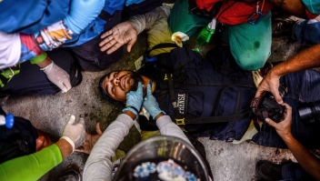 A wounded journalist is helped by volunteer medics during clashes between opposition demonstrators and riot police ensuing an anti-government protest in Caracas, on July 26, 2017. Venezuelans blocked off deserted streets Wednesday as a 48-hour opposition-led general strike aimed at thwarting embattled President Nicolas Maduro's controversial plans to rewrite the country's constitution got underway. / AFP PHOTO / FEDERICO PARRA (Photo credit should read FEDERICO PARRA/AFP/Getty Images)