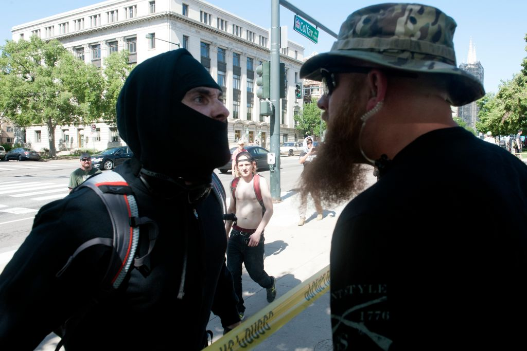 An Antifa demonstrator has a heated exchange with a pro-Trump supporter during the Denver March Against Sharia Law in Denver, Colorado on June 10, 2017. The march was supported by two right-wing groups, The Proud Boys, and Bikers Against Radical Islam. Police kept the counter protestors separated during the rally which was held in front of the Colorado State Capital. The march was one of many held throughout the U.S. opposing Sharia law, and was viewed by many as promoting both Islamophobia and racism. / AFP PHOTO / Jason Connolly (Photo credit should read JASON CONNOLLY/AFP/Getty Images)