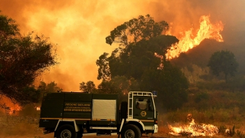 Esta fotografía tomada el 10 de julio de 2017 muestra un vehículo de rescate de incendios en el districto de Annunziata, en Messina, en medio de las llamas. En todo el país, los bomberos italianos han intervenido más de mil veces en los últimos días para combatir los incendios. Crédito: GIOVANNI ISOLINO / AFP / Getty Images