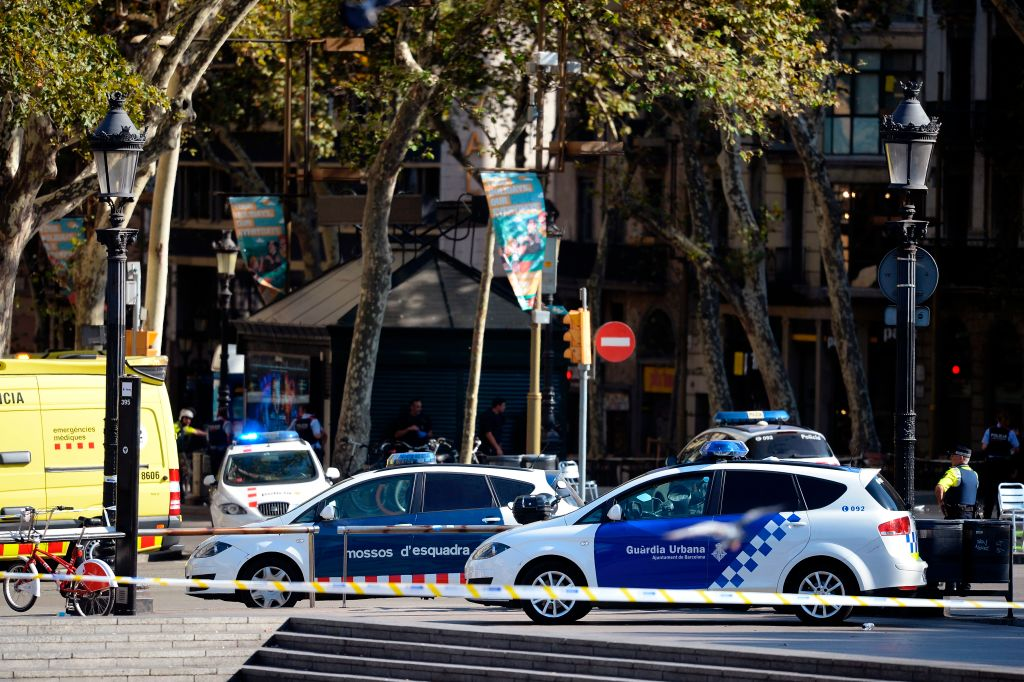 Policemen stand next to vehicles in a cordoned off area after a van ploughed into the crowd, injuring several persons on the Rambla in Barcelona on August 17, 2017. / AFP PHOTO / Josep LAGO (Photo credit should read JOSEP LAGO/AFP/Getty Images)