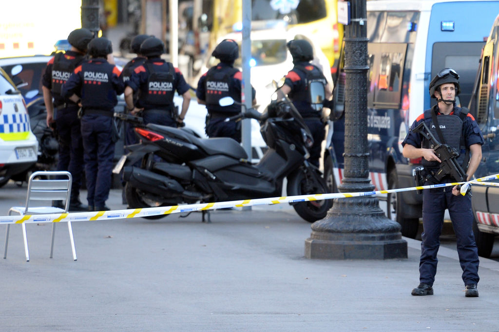 """Armed policemen stand in a cordoned off area after a van ploughed into the crowd, injuring several persons on the Rambla in Barcelona on August 17, 2017. Police in Barcelona said they were dealing with a """"terrorist attack"""" after a vehicle ploughed into a crowd of pedestrians on the city's famous Las Ramblas boulevard on August 17, 2017. Police were clearing the area after the incident, which has left a number of people injured. / AFP PHOTO / Josep LAGO (Photo credit should read JOSEP LAGO/AFP/Getty Images)"""