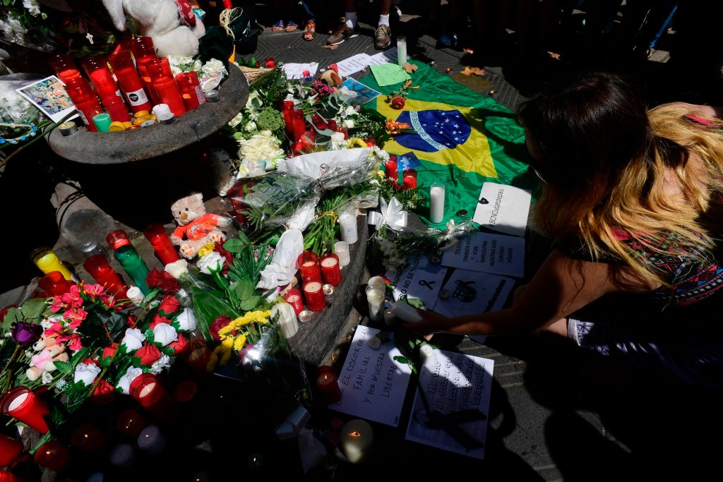 A woman displays a candle next to flowers, messages, stuffed toys and many differents objects for the victims on August 18, 2017 on the spot where yesterday a van ploughed into the crowd, killing 13 persons and injuring over 100 on the Rambla boulevard in Barcelona. Drivers have ploughed on August 17, 2017 into pedestrians in two quick-succession, separate attacks in Barcelona and another popular Spanish seaside city, leaving 13 people dead and injuring more than 100 others. In the first incident, which was claimed by the Islamic State group, a white van sped into a street packed full of tourists in central Barcelona on Thursday afternoon, knocking people out of the way and killing 13 in a scene of chaos and horror. Some eight hours later in Cambrils, a city 120 kilometres south of Barcelona, an Audi A3 car rammed into pedestrians, injuring six civilians -- one of them critical -- and a police officer, authorities said. / AFP PHOTO / JAVIER SORIANO (Photo credit should read JAVIER SORIANO/AFP/Getty Images)