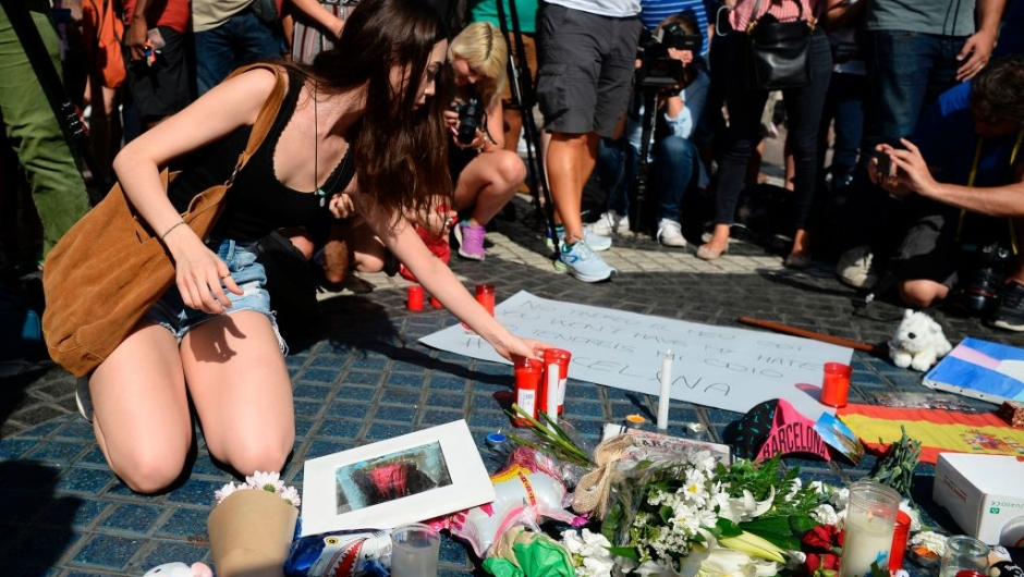 A woman displays candles on the Rambla boulevard for the victims of the Barcelona attack on August 18, 2017, a day after a van ploughed into the crowd, killing 13 persons and injuring over 100 on the Rambla in Barcelona. Drivers have ploughed on August 17, 2017 into pedestrians in two quick-succession, separate attacks in Barcelona and another popular Spanish seaside city, leaving 13 people dead and injuring more than 100 others. In the first incident, which was claimed by the Islamic State group, a white van sped into a street packed full of tourists in central Barcelona on Thursday afternoon, knocking people out of the way and killing 13 in a scene of chaos and horror. Some eight hours later in Cambrils, a city 120 kilometres south of Barcelona, an Audi A3 car rammed into pedestrians, injuring six civilians -- one of them critical -- and a police officer, authorities said. / AFP PHOTO / Josep LAGO (Photo credit should read JOSEP LAGO/AFP/Getty Images)