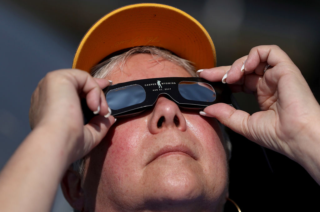 """CASPER, WY - AUGUST 21: A visitor looks at the solar eclipse at South Mike Sedar Park on August 21, 2017 in Casper, Wyoming. Millions of people have flocked to areas of the U.S. that are in the """"path of totality"""" in order to experience a total solar eclipse. During the event, the moon will pass in between the sun and the Earth, appearing to block the sun. (Photo by Justin Sullivan/Getty Images)"""