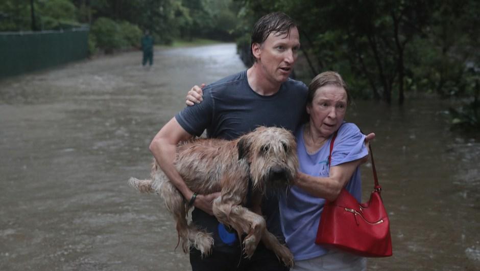 Andrew White (izq.) ayuda a una vecina después de rescatarla de su hogar en su barco en el barrio de River Oaks el 27 de agosto de 2017 en Houston, Texas. Crédito: Scott Olson / Getty Images