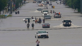 People walk through the flooded waters of Telephone Rd. in Houston on August 27, 2017 as the US fourth city city battles with tropical storm Harvey and resulting floods. / AFP PHOTO / Thomas B. Shea (Photo credit should read THOMAS B. SHEA/AFP/Getty Images)