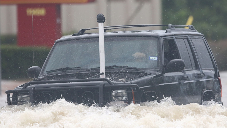 A SUV with a tube connected to his exhaust drives through the flooded waters on Telephone Rd. in Houston on August 27, 2017 as the US fourth city city battles with tropical storm Harvey and resulting floods. / AFP PHOTO / Thomas B. Shea (Photo credit should read THOMAS B. SHEA/AFP/Getty Images)
