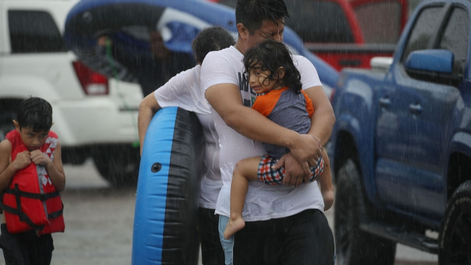 HOUSTON, TX - AUGUST 27: Mario Qua holds Wilson Qua as they evacuate their flooded home after the area was inundated with flooding from Hurricane Harvey on August 27, 2017 in Houston, Texas. Harvey, which made landfall north of Corpus Christi late Friday evening, is expected to dump upwards to 40 inches of rain in Texas over the next couple of days. (Photo by Joe Raedle/Getty Images)