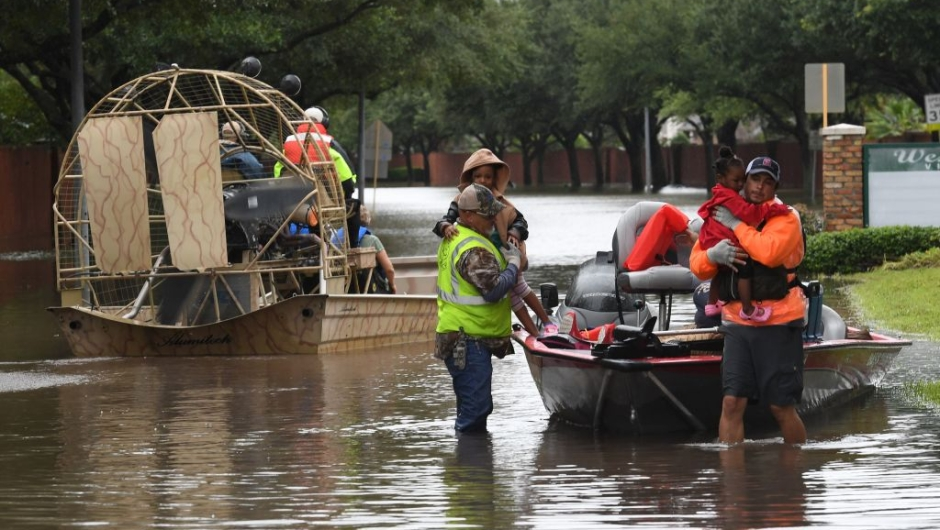 Local residents are evacuated by volunteers from San Antonio, in the Clodine district after Hurricane Harvey caused heavy flooding in Houston, Texas on August 29, 2017. Floodwaters have breached a levee south of the city of Houston, officials said Tuesday, urging residents to leave the area immediately. / AFP PHOTO / MARK RALSTON (Photo credit should read MARK RALSTON/AFP/Getty Images)