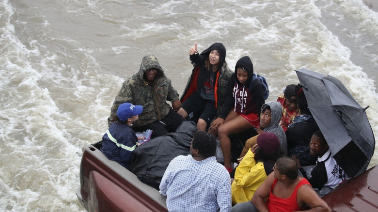 PORT ARTHUR, TX - AUGUST 30: Evacuees ride in the back of a pickup truck after the area was inundated with flooding of Hurricane Harvey on August 30, 2017 in Port Arthur, Texas. Harvey, which made landfall north of Corpus Christi late Friday evening, is expected to dump upwards to 40 inches of rain in Texas over the next couple of days. (Photo by Joe Raedle/Getty Images)