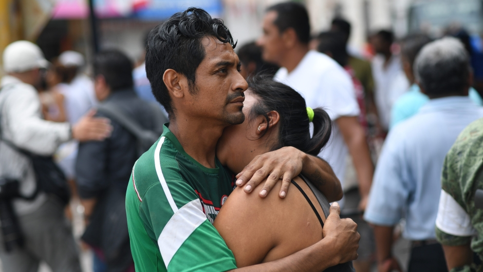 A couple embraces on September 8, 2017 in Juchitan de Zaragoza, state of Oaxaca, where buildings collapsed after an 8.2 earthquake that hit Mexico's Pacific coast overnight. Mexico's most powerful earthquake in a century killed at least 35 people, officials said, after it struck the Pacific coast, wrecking homes and sending families fleeing into the streets. / AFP PHOTO / Pedro PARDO (Photo credit should read PEDRO PARDO/AFP/Getty Images)