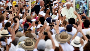"""Pope Francis waves from the Popemobile upon arrival at Contecar -Cartagena's maritime terminal- to celebrate an open-air mass during the last day of his visit to Colombia on September 10, 2017. Pope Francis prayed Sunday for a peaceful end to Venezuela's """"grave crisis"""" which has left scores dead, as he wrapped up a tour to support peace in neighboring Colombia. / AFP PHOTO / Alberto PIZZOLI (Photo credit should read ALBERTO PIZZOLI/AFP/Getty Images)"""