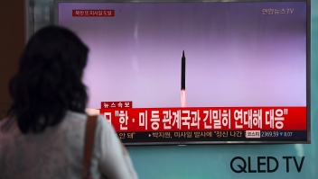 A woman watches a screen showing file footage of a North Korean missile launch, at a railway station in Seoul on September 15, 2017. North Korea fired an intermediate range ballistic missile eastwards over Japan and into the Pacific on September 15, the US said, its latest provocation amid high tensions over its banned weapons programmes. / AFP PHOTO / JUNG Yeon-Je (Photo credit should read JUNG YEON-JE/AFP/Getty Images)