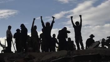 El puño alzado, un símbolo y una orden: silencio. Podría haber una vida en juego entre los escombros. Crédito: PEDRO PARDO / AFP / Getty Images.