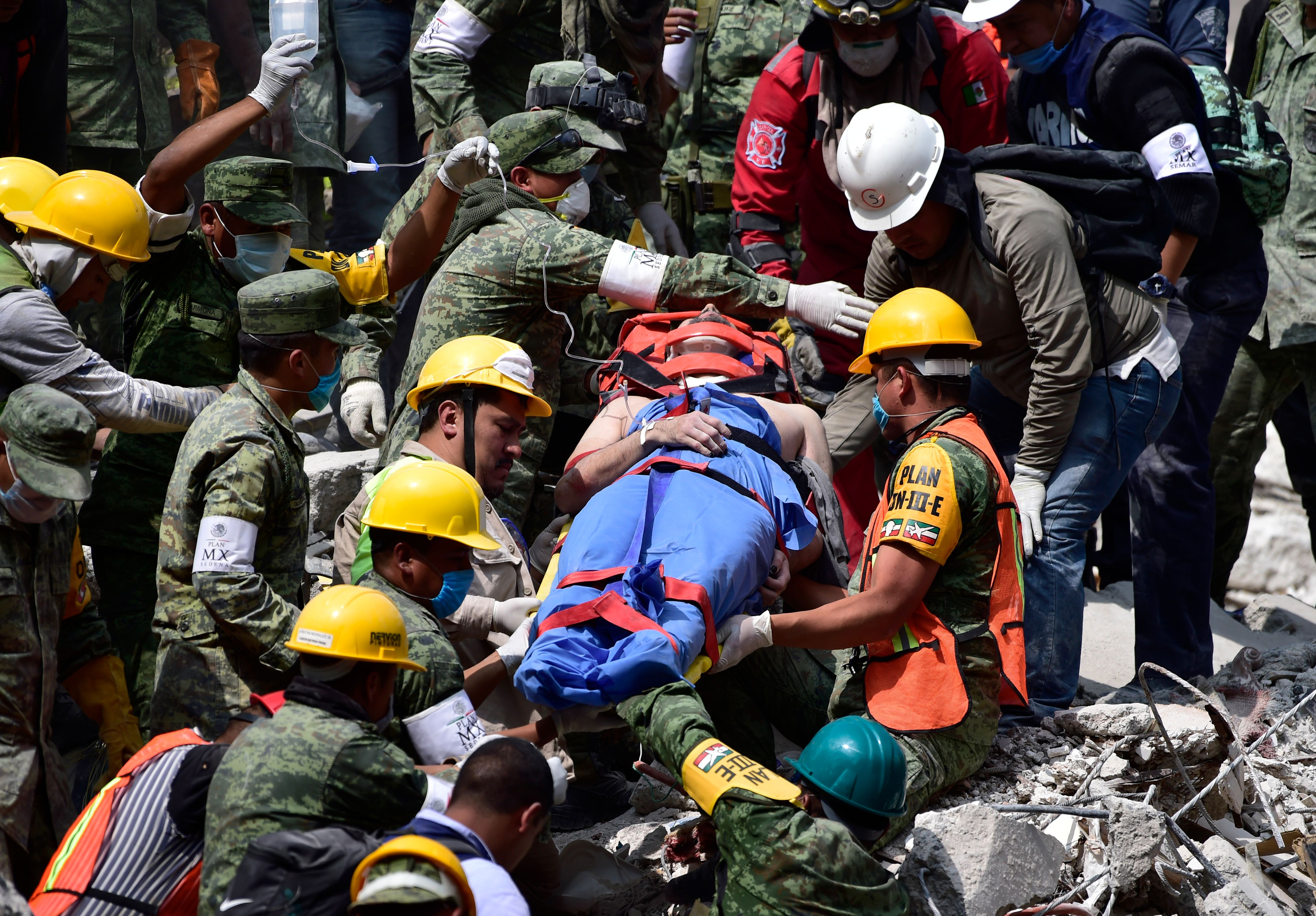 A survivor is pulled out of the rubble from a flattened building in Mexico City on September 20, 2017 as the search for survivors continues a day after a strong quake hit central Mexico. A powerful 7.1 earthquake shook Mexico City on Tuesday, causing panic among the megalopolis' 20 million inhabitants on the 32nd anniversary of a devastating 1985 quake. / AFP PHOTO / Pedro PARDO (Photo credit should read PEDRO PARDO/AFP/Getty Images)