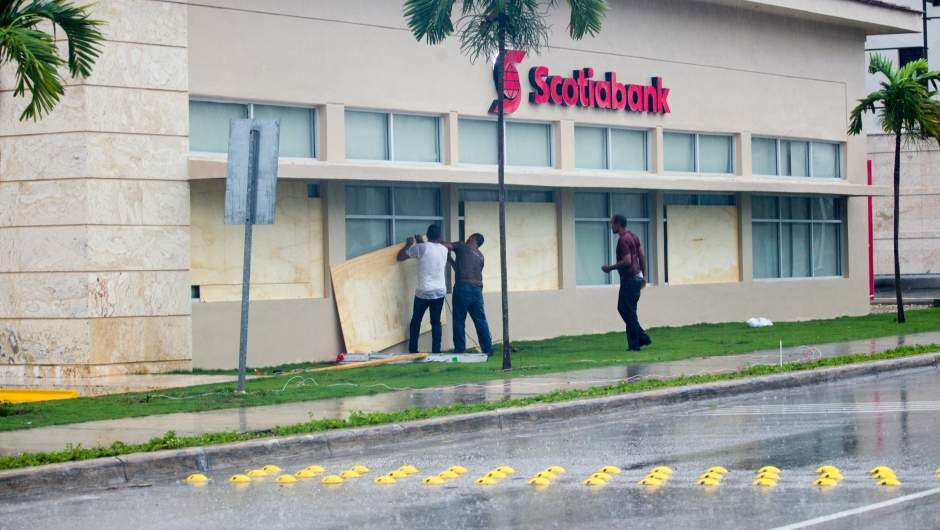 Workers cover the windows of a bank in Punta Cana, in the Dominican Republic, as Hurricane Maria approaches on September 20, 2017. The government of the Dominican Republic told people to stay home from their public and private sector jobs on Thursday, when the hurricane is expected to hit the island. / AFP PHOTO / Erika SANTELICES (Photo credit should read ERIKA SANTELICES/AFP/Getty Images)