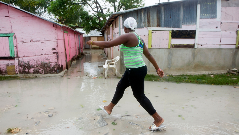 A woman walks along a flooded street in Punta Cana, in the Dominican Republic, as Hurricane Maria approaches on September 20, 2017. The government of the Dominican Republic told people to stay home from their public and private sector jobs on Thursday, when the hurricane is expected to hit the island. / AFP PHOTO / Erika SANTELICES (Photo credit should read ERIKA SANTELICES/AFP/Getty Images)