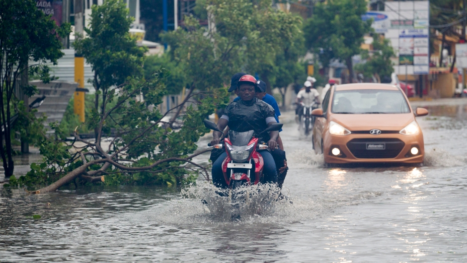 People drive along a flooded street in Punta Cana, in the Dominican Republic, as Hurricane Maria approaches on September 20, 2017. The government of the Dominican Republic told people to stay home from their public and private sector jobs on Thursday, when the hurricane is expected to hit the island. / AFP PHOTO / Erika SANTELICES (Photo credit should read ERIKA SANTELICES/AFP/Getty Images)