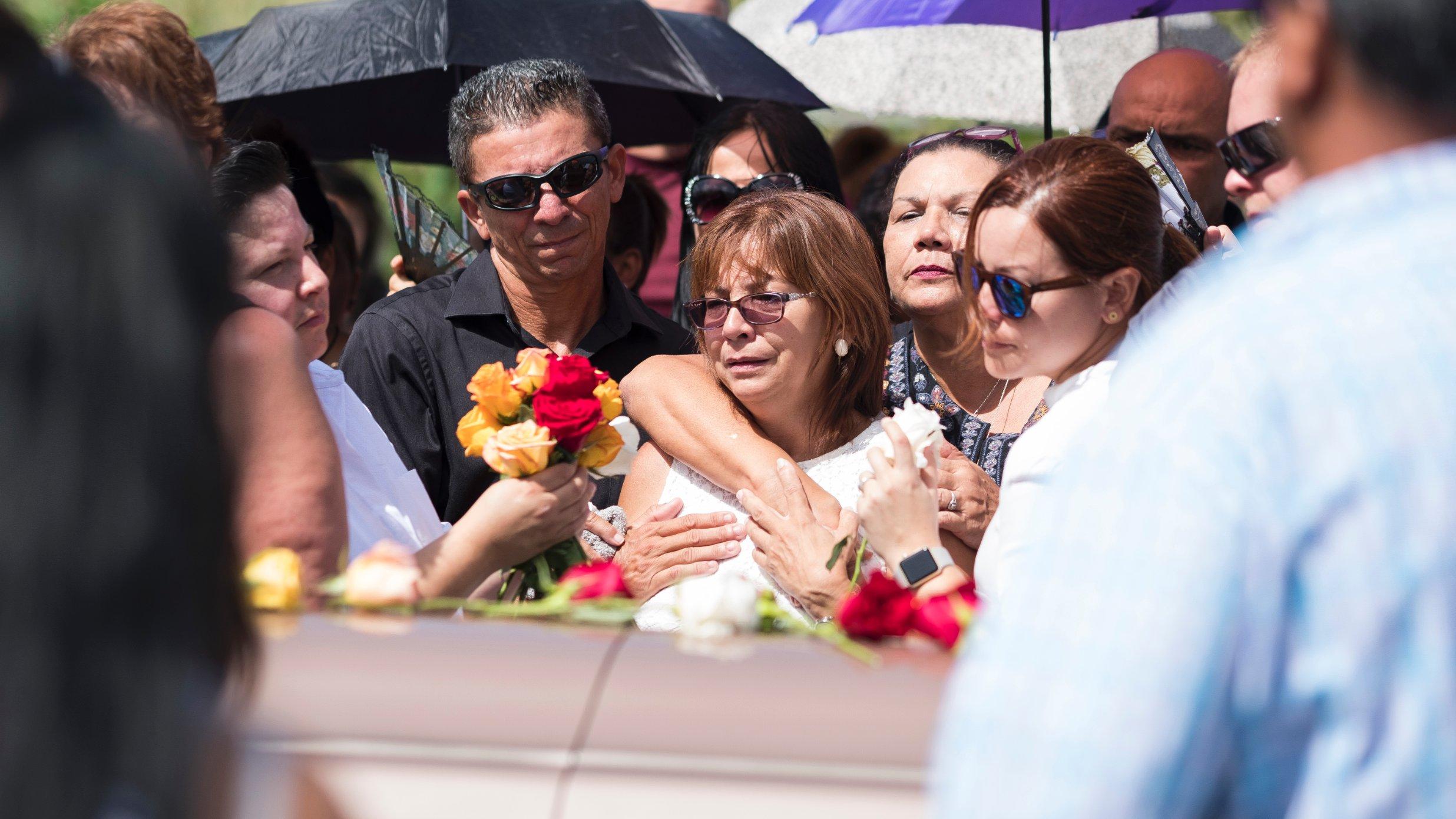 Evelyn Cruz Rivera, una de los cinco hijos de Isabel Rivera, junto al ataúd de su madre.