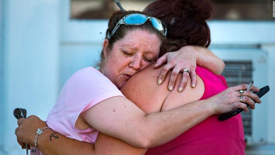 Carrie Matula abraza a una mujer después del tiroteo en la iglesia. Matula dijo que escuchó los disparos desde la gasolinera donde trabaja al otro lado de la calle.