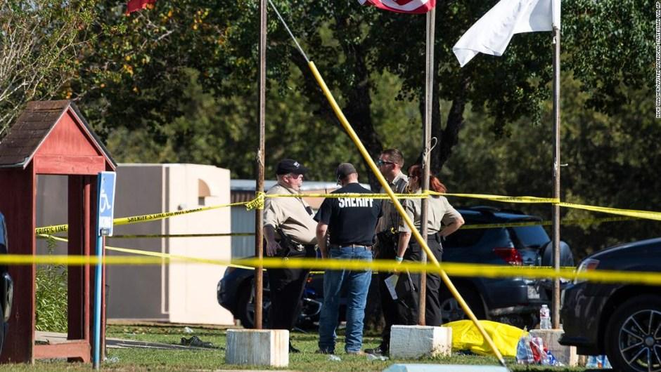 Policías junto a un cadáver cubierto en el lugar de los hechos.