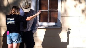 Una mujer reza con un hombre después del tiroteo.