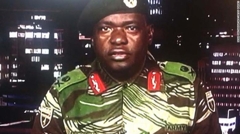 """TOPSHOT - This screen grab taken early on November 15, 2017 from a television broadcast on the Zimbabwe Broadcasting corporation (ZBC) shows Zimbabwe Major General Sibusiso Moyo reading a statement at the ZBC broadcast studio in Harare. Zimbabwe's military appeared to be in control of the country on November 15 as generals denied staging a coup but used state television to vow to target """"criminals"""" close to President Robert Mugabe. / AFP PHOTO / Dewa MAVHINGA (Photo credit should read DEWA MAVHINGA/AFP/Getty Images)"""