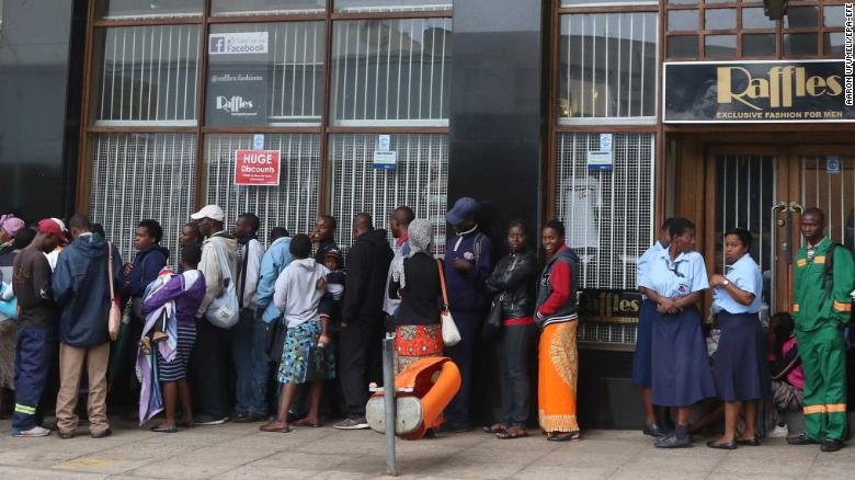 epa06330392 Members of the public wait outside a bank to withdraw cash in Harare, Zimbabwe, 15 November 2017. The Zimbabwe National Army (ZNA) has reportedly taken control over the government of President Robert Mugabe. The army seized the national broadcaster's headquarters (ZBC) on 14 November night, to announce that President Mugabe and his family were safe but without citing their whereabouts. The military denied it staged a coup d'etat. EPA-EFE/AARON UFUMELI