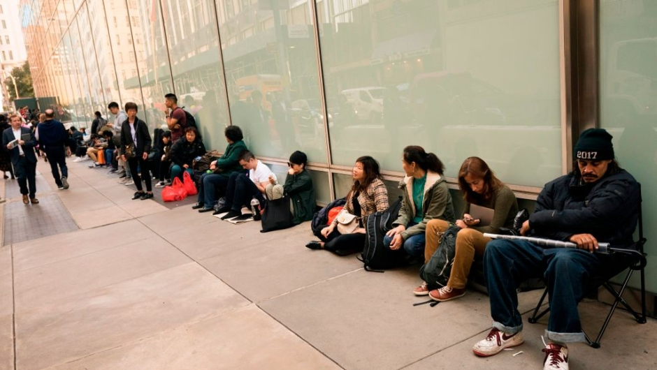 People line up outside the 5th Avenue Apple store on November 2, 2017, in New York. People are queueing up early to get their hands on the new iPhone X. / AFP PHOTO / Don Emmert (Photo credit should read DON EMMERT/AFP/Getty Images)