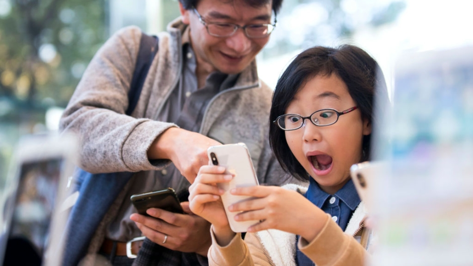 TOKYO, JAPAN - NOVEMBER 03: A girl reacts as she tries an iPhone X at the Apple Omotesando store on November 3, 2017 in Tokyo, Japan. Apple launched the latest iPhone featuring face recognition technology, a large 5.8-inch edge-to-edge high resolution OLED display and better front and back cameras with optical image stabilisation today. (Photo by Tomohiro Ohsumi/Getty Images)
