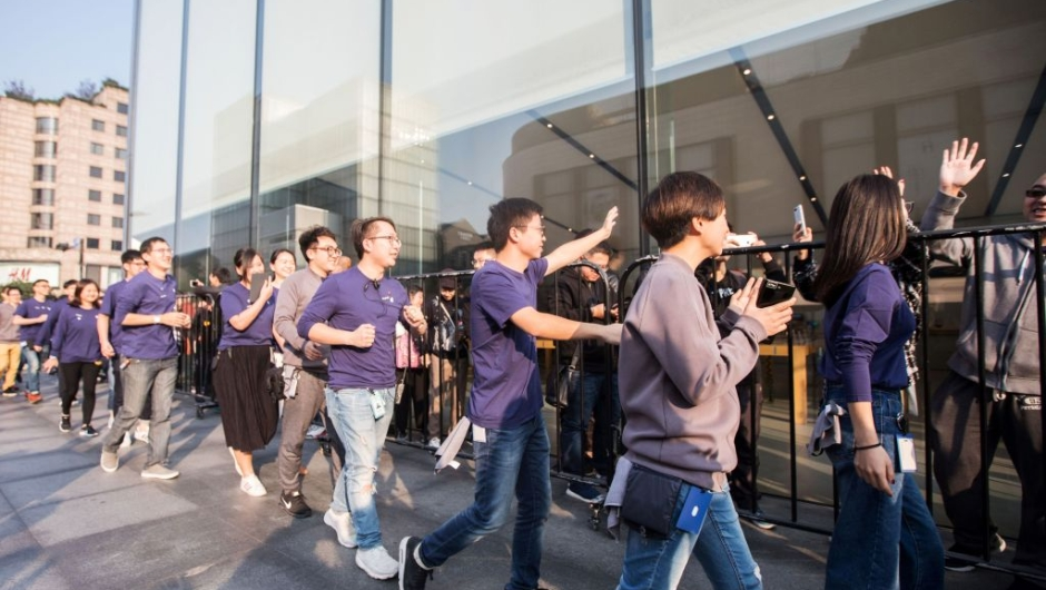 Apple employees (in blue) wave to Chinese customers as they queue up outside the Apple store to get their hands on the new iPhone X in Hangzhou in China's eastern Zhejiang province on November 3, 2017. Apple profits soared by a fifth as its flagship iPhone X hit stores in Asia on November 3, with the company predicting bumper sales despite its eye-watering price tag. / AFP PHOTO / STR / China OUT (Photo credit should read STR/AFP/Getty Images)
