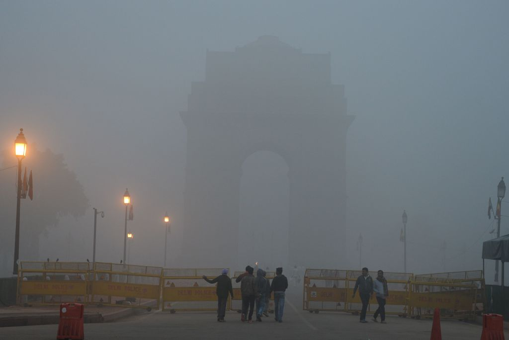 Indian pedestrians walk near the India Gate monument amid heavy smog in New Delhi on November 8, 2017. Delhi shut all primary schools on November 8 as pollution levels hit nearly 30 times the World Health Organization safe level, prompting doctors in the Indian capital to warn of a public health emergency. Dense grey smog shrouded the roads of the world's most polluted capital, where many pedestrians and bikers wore masks or covered their mouths with handkerchiefs and scarves. / AFP PHOTO / SAJJAD HUSSAIN (Photo credit should read SAJJAD HUSSAIN/AFP/Getty Images)