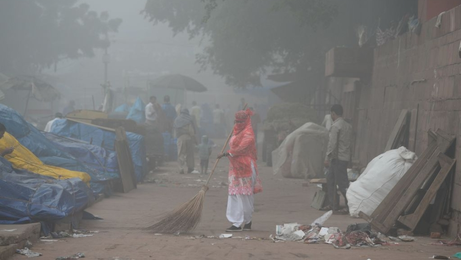 An Indian sweeper cleans a road amid heavy smog in New Delhi on November 8, 2017. Delhi shut all primary schools on November 8 as pollution levels hit nearly 30 times the World Health Organization safe level, prompting doctors in the Indian capital to warn of a public health emergency. Dense grey smog shrouded the roads of the world's most polluted capital, where many pedestrians and bikers wore masks or covered their mouths with handkerchiefs and scarves. / AFP PHOTO / SAJJAD HUSSAIN (Photo credit should read SAJJAD HUSSAIN/AFP/Getty Images)