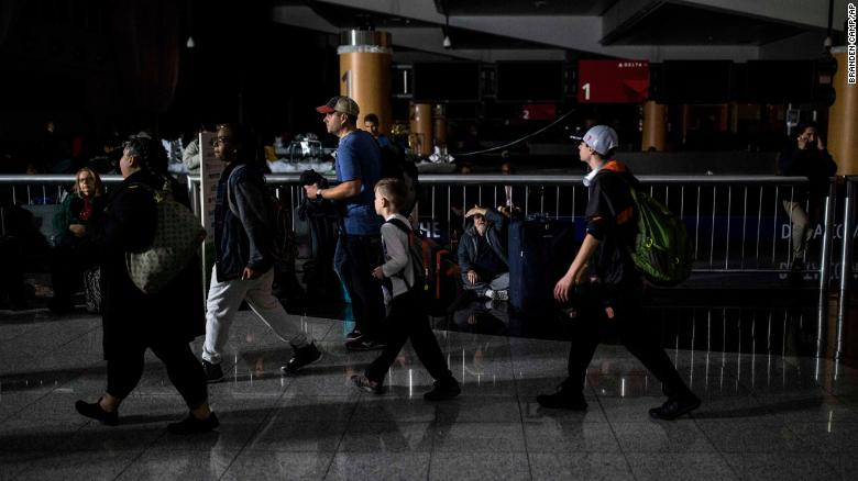 Passengers make their way through Hartfield-Jackson Atlanta International Airport after the lights went out at the airport, Sunday, Dec. 17, 2017, in Atlanta. A sudden power outage at the airport on Sunday grounded scores of flights and passengers during one of the busiest travel times of the year. (AP Photo/Branden Camp)