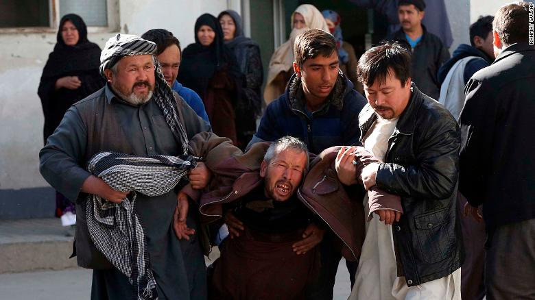 A distraught man is carried following a suicide attack in Kabul, Afghanistan, Thursday, Dec. 28, 2017. Authorities say attackers stormed the Shiite Muslim cultural center in the Afghan capital Kabul, setting off multiple bombs and killing dozens. (AP Photo/Rahmat Gul)