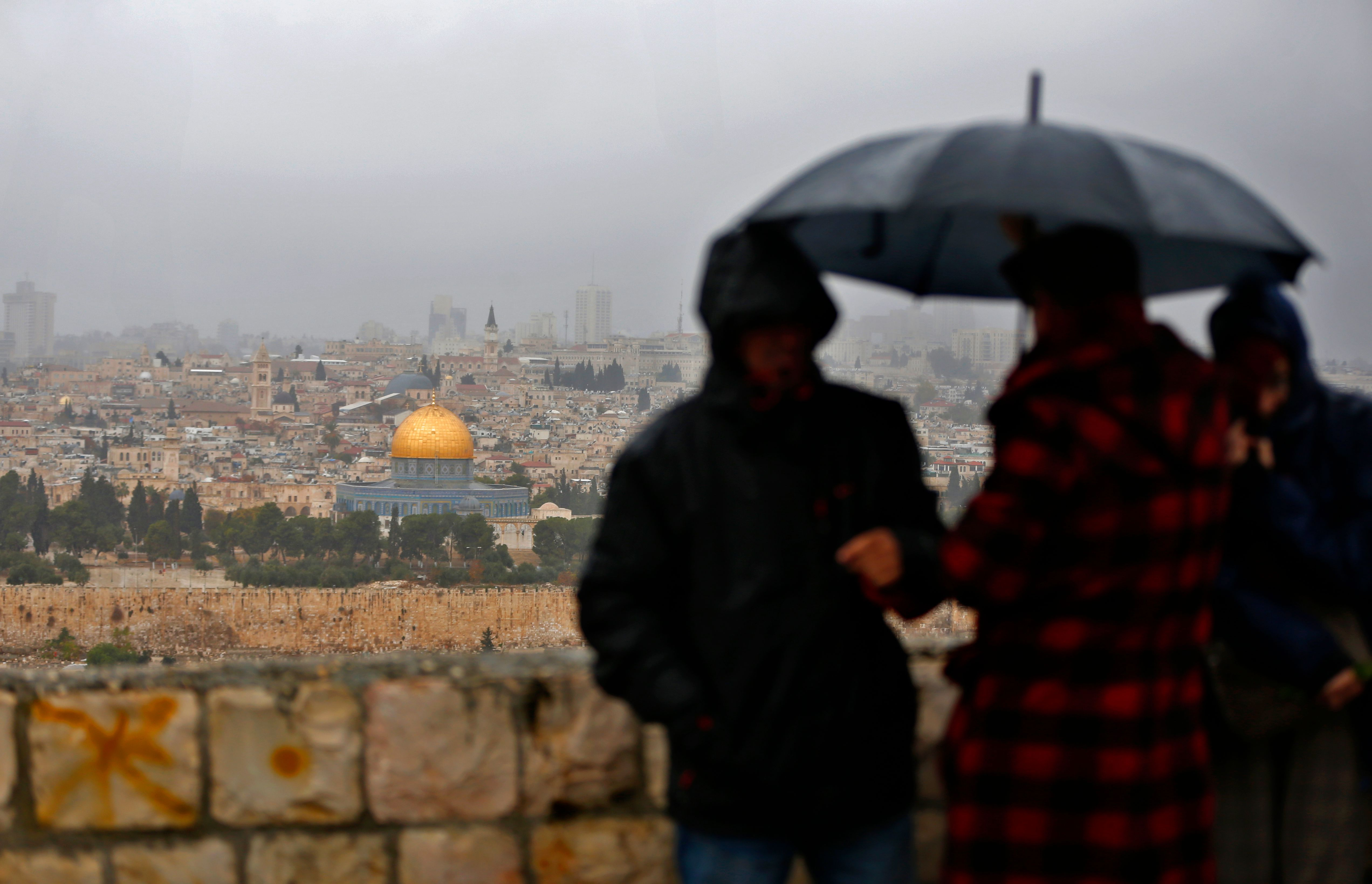 People stand at Mount of Olives and look at the Old City of Jerusalem and its Dome of the Rock mosque in the centre, on December 6, 2017. President Donald Trump is set to recognise Jerusalem as Israel's capital, upending decades of careful US policy and ignoring dire warnings from Arab and Western allies alike of a historic misstep that could trigger a surge of violence in the Middle East. / AFP PHOTO / AHMAD GHARABLI (Photo credit should read AHMAD GHARABLI/AFP/Getty Images)
