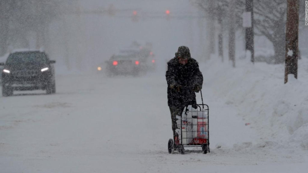 A man walks with his groceries in a cart, Friday, Dec. 29, 2017, in Erie, Pa. The cold weather pattern was expected to continue through the holiday weekend and likely longer, according to the National Weather Service, prolonging a stretch of brutal weather blamed for several deaths, crashes and fires. (AP Photo/Tony Dejak)