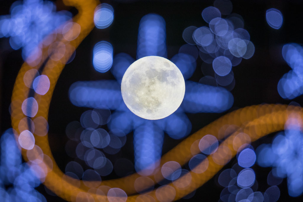 """WELLS, ENGLAND - JANUARY 01: The first full moon of 2018 rises behind festive seasonal lights on display in the High Street in Wells on January 1, 2018 in Somerset, England. Tonight's full moon, which is known by Native American tribes as the """"Wolf Moon"""", is also a supermoon which means it coincides with the Moon's closest approach to Earth, known as the perigee. Tonights Wolf Moon is the first of two full moons in January. The second will take place on the night of January 31 and in some areas of the world this will also happen at the same time as a total lunar eclipse. (Photo by Matt Cardy/Getty Images)"""