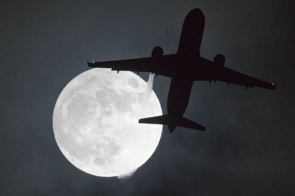 """TOPSHOT - A plane flys in front of a """"super moon"""" or """"wolf moon"""" on its approach to London Heathrow Airport on January 1, 2018. / AFP PHOTO / Justin TALLIS (Photo credit should read JUSTIN TALLIS/AFP/Getty Images)"""