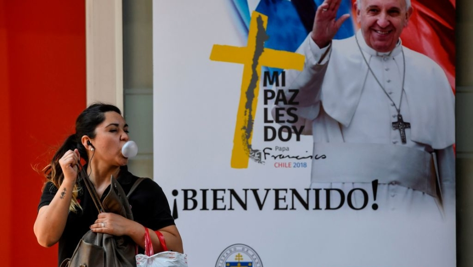 A woman blows a bubble with chewing gum, as she walks past a welcome poster with the image of Pope Francis, ahead of his upcoming visit to Santiago on January 11, 2018. Pope Francis will be visiting Chile from January 15 to 18. / AFP PHOTO / Martin BERNETTI (Photo credit should read MARTIN BERNETTI/AFP/Getty Images)